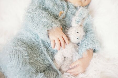 Newborn Baby. Sleeping Baby In Bed, Holding A Bunny Toy. Baby With Blue Knitted Romper