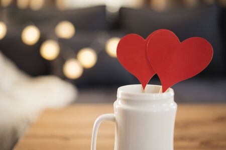 Valentines Day Red Heart Tags In White Mug  On The Coffee Table. Sofa In The Background. Red Heart Mock Up. Valentine Day Concept. Branding Mockup Zdjęcie Seryjne