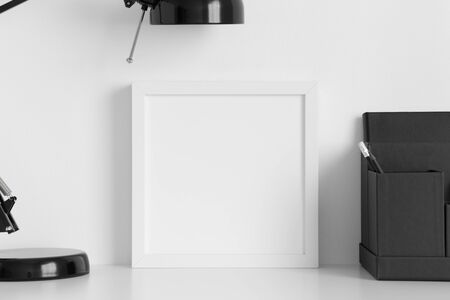 White square frame mockup with a lamp and workspace accessories on a white table. Zdjęcie Seryjne