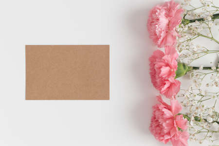 Top view of a kraft card mockup with gypsophila and pink carnations on a white table.