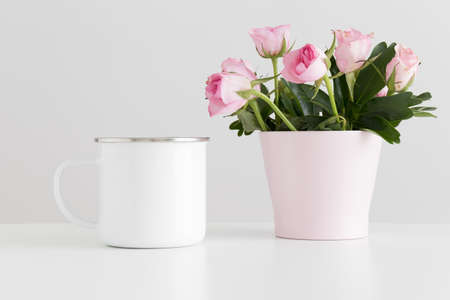 Enamel mug mockup with pink roses in a pot on a white table.
