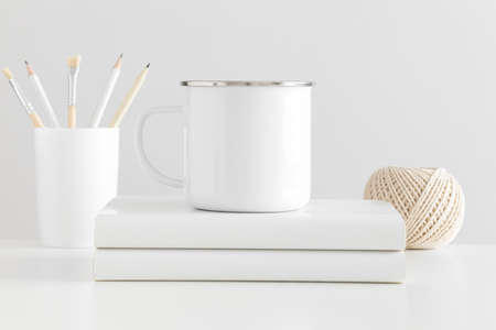 Enamel mug mockup with workspace accessories on a white table.