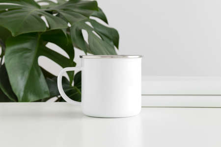 Enamel mug mockup with workspace accessories and a monstera plant.