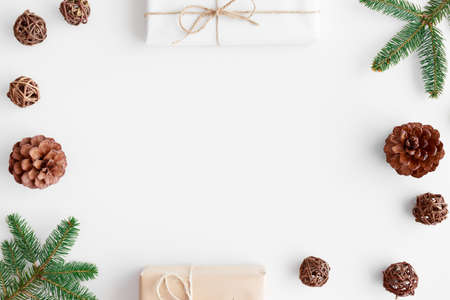 Christmas gifts with pine cones and leaves on a white table. Flat lay with blank copy space.