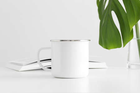 Enamel mug mockup with a monstera leaf in a vase and a book on a white table.