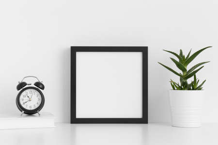 Black square frame mockup with a aloe vera in a pot and workspace accessories on a white table. Imagens