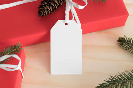 White blank tag mockup isolated on a red christmas gift.