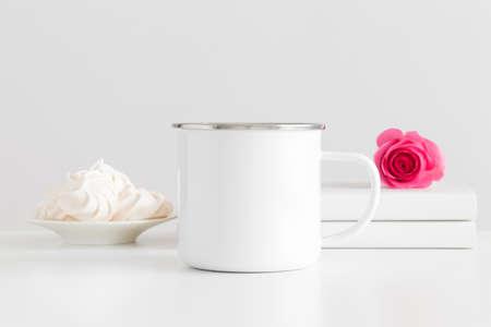 Enamel mug mockup with books and a pink rose on a white table. Zdjęcie Seryjne