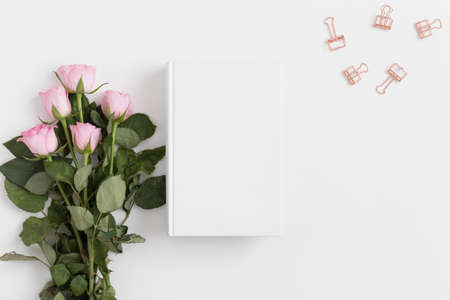 White book mockup with a bouquet of pink roses and workspace accessories on a white table.