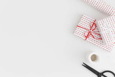 White gifts, twine, scissors and paper roll on a white table. Flat lay with blank copy space.