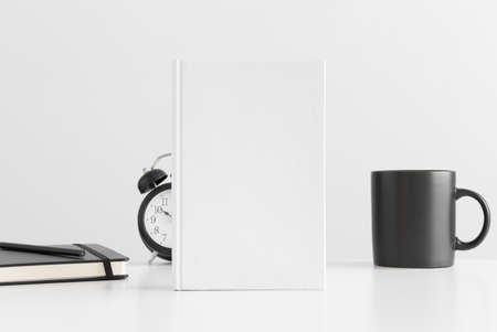 White book mockup with a mug, clock and notebook on a white table.