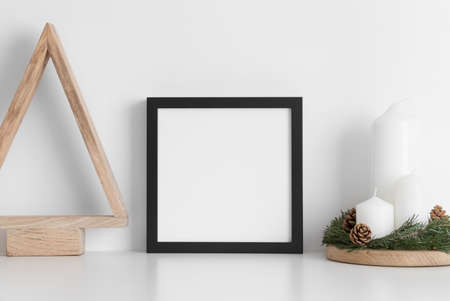Black square frame mockup with a wooden tree and candles on a white table. Christmas decoration.