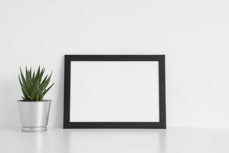 Black frame mockup with a cactus in a pot on a white table.Landscape orientation.