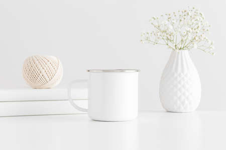 Enamel mug mockup with workspace accessories and a gypsophila on a white table.