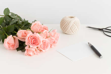 White card, bouquet of pink roses and a twine on a white table.