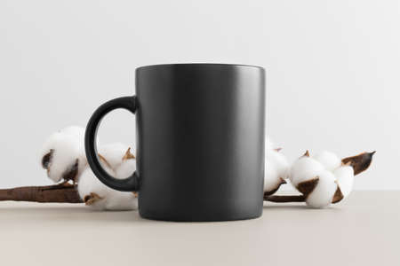 Black mug mockup with a cotton branch on a beige table. Stockfoto