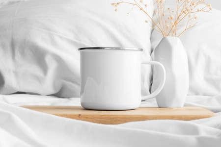 Enamel mug mockup and a gypsophila on the bed.