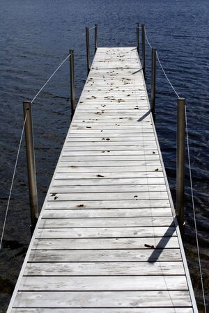 long dock with goose droppings in northern michigan on a small lake photo