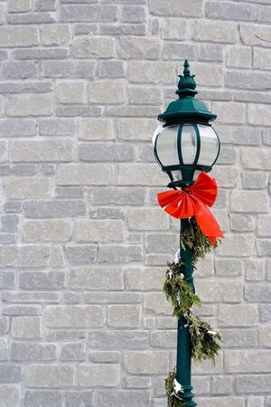 lampost: green lampost against a white brick wall wrapped in garland with a little snow on it