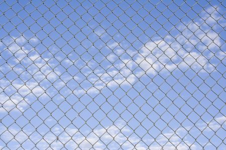 Close up of fence with a blue cloudy sky in the background photo