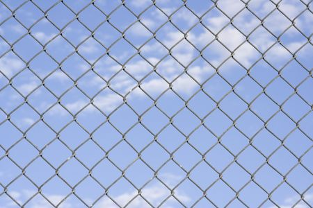 Close up of fence with a blue cloudy sky in the background
