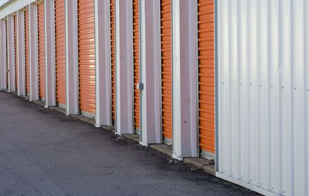 Row of orange door from a storage warehouse alarm system seen at the bottom of each door photo