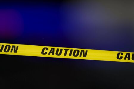 Caution tape over a black background with flashing lights in the background photo