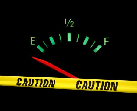 gas gauge: Gas gauge bright colors on empty on a black background with yellow caution tape across the front of it