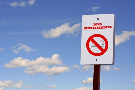 abstain: No smoking sign on a post against a blue sky with puffy white clouds