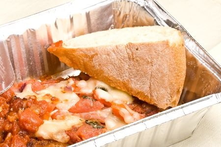 carry out meal chicken parmesan with a slice of bread in the carry out container Reklamní fotografie