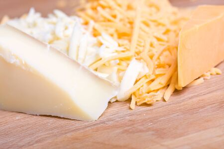 yellow and white cheddar cheese grated on a wood cutting board