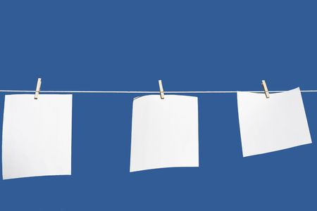 paper hanging from a clothes line with a blue background photo