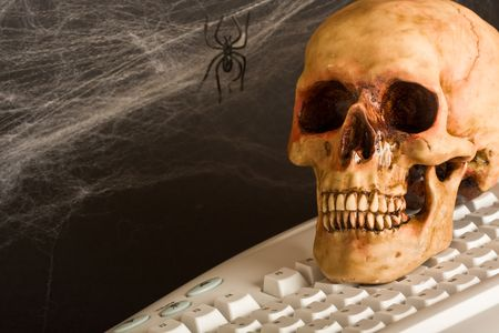 concept shot of how slow the internet can be skull on a keyboard with cobwebs in the background photo
