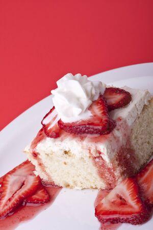 ストロベリー ショート ケーキ赤い背景の上の果実をスライスし、ホイップ クリーム 写真素材