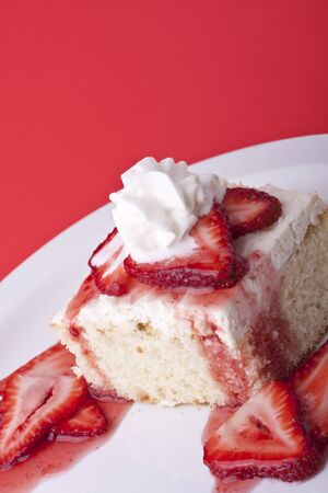 strawberry shortcake on a red background sliced berries and whipped cream Stock Photo