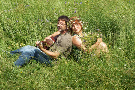 The pair sits on a meadow with a guitar