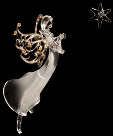 white glass angel and star on black background photo