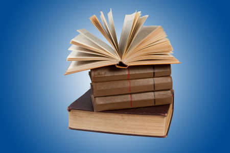 Stack of books against blue gradient background Stock Photo