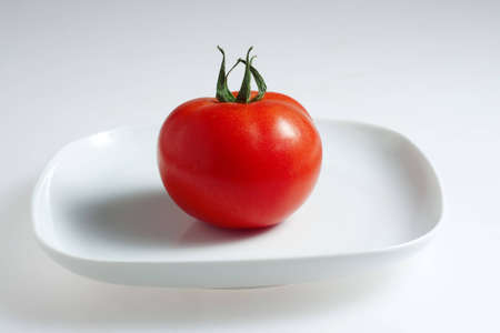 Red tomato on a white plate
