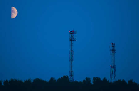 Aerials of cellular communication and moon at night