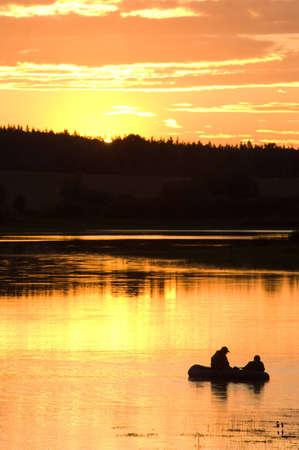 Fishermen in lake on sunset Stock Photo