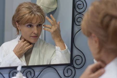 the reflexion of woman looking in mirror photo