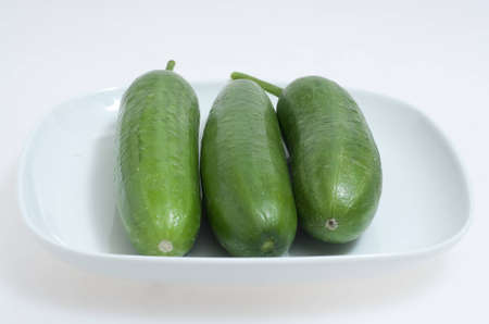 green cucumbers on a white plate Stock Photo