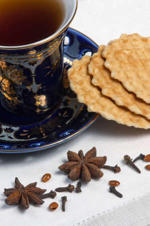 close-up of  teacup, spices and cookies on table