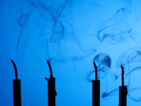 Extinguished candles with smoke on blue background