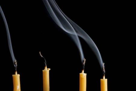 Extinguished candles with smoke on black background