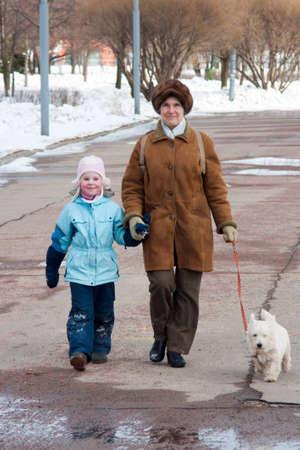 senioren wandelen: De grootmoeder met de kleindochter en hond op loopafstand