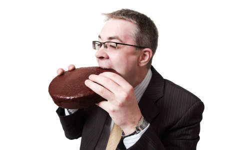 young businessman bites chocolate pie Stock Photo