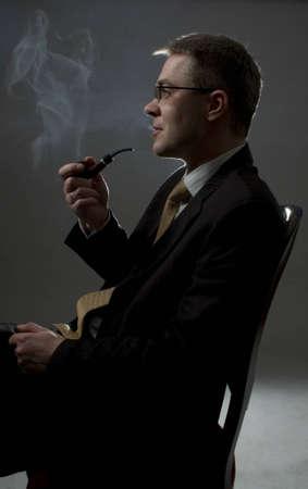 profile of sitting businessman smoking  tube Stock Photo