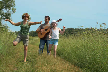 Parents with the daughter walk on a meadow Stock Photo - 12544556